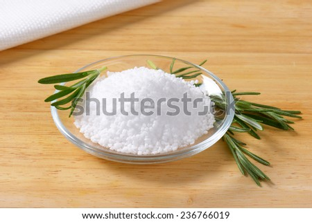 coarse salt with sprig of rosemary in the glass bowl
