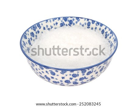 Coarse sea salt in a blue and white porcelain bowl with a floral design, isolated on a white background - stock photo