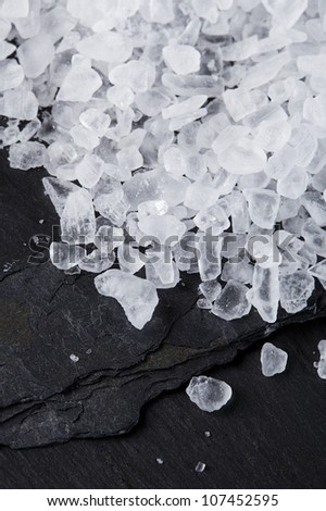 Coarse sea salt on black slate stone background, closeup - stock photo