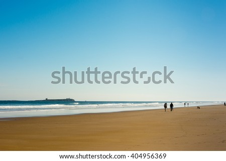Coast at Bamburgh in Northumberland England at dusk with Farne Islands in the background - stock photo