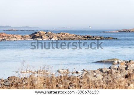 Coast, cliffs, islands and a distant beacon surrounded with fog a sunny day during spring time in scandinavia - stock photo