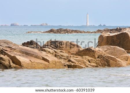 Coast of Bretagne with lighthouse near Ploumanach in France - stock photo