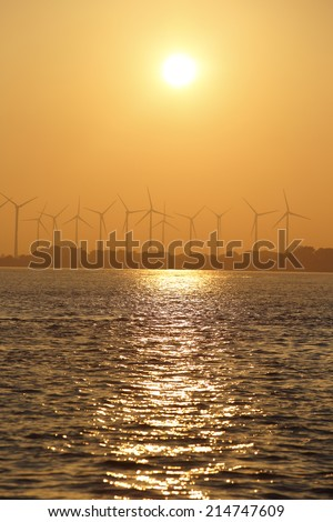 coast onshore wind power station in sunset - stock photo