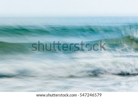 Coastal abstract motion blurred ocean waves blue tones background sea spray wind blown off surface