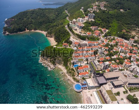 Coastal asphalt road passing through the Budva city, over the Mogran beach. Aerial shot. Montenegro