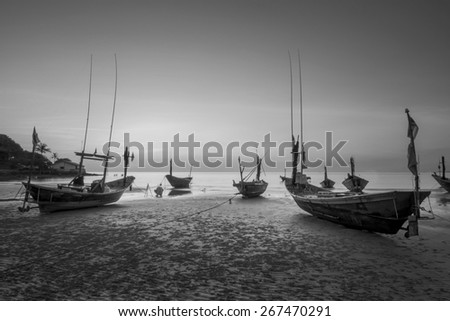 Coastal fishing boats moored at the seaside. With sunset light black and white tones. - stock photo