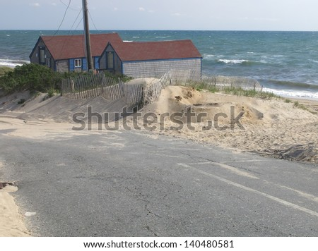 Coastal landscape: Asphalt road by sand dune, pair of beach cottages facing west, and Cape Cod Bay - stock photo