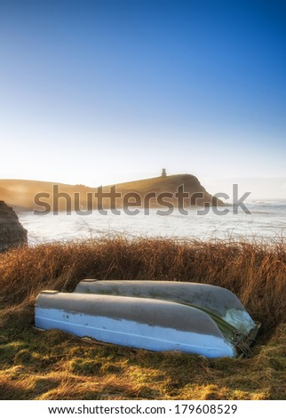 Coastal landscape at sunrise with cliffs and misty glow with old rowing boat foreground - stock photo