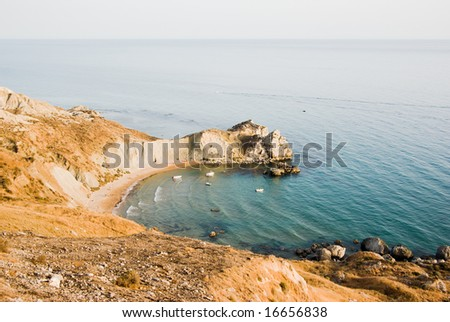 coastal landscape of a bay with bather  and boats - stock photo