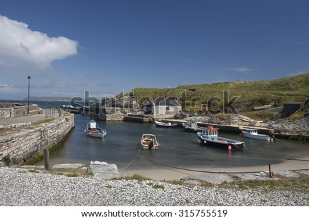 Coastal landscape showing rocky beaches and harbour at Balintoy in County Antrim in UK on the Atlantic north west coast of Ireland on a sunny day with  blue skies with clouds and moored boats.