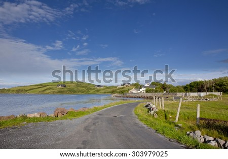 Coastal landscape showing scenic coastal fields houses on Clew Bay at Westport in County Mayo on west coast of Ireland overlooking the Atlantic on a calm sunny day with blue skies with clouds. - stock photo
