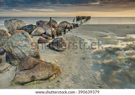 Coastal landscape with stones and wooden column of old broken wharf, Baltic Sea - stock photo