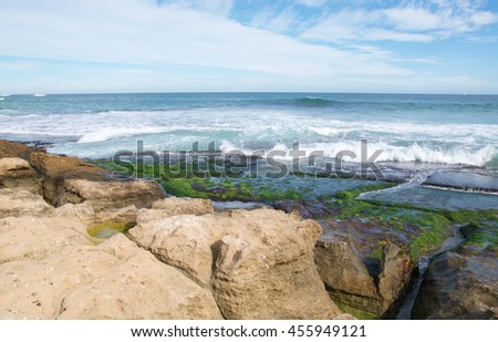 Coastal limestone and Indian Ocean seascape under a blue sky with clouds at Penguin Island in Rockingham, Western Australia/Seascape and Limestone/Penguin Island, Rockingham, Western Australia - stock photo