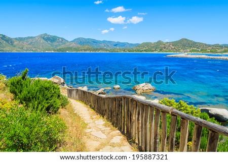 Coastal path along a beautiful bay with azure sea water near Porto Giunco port, Sardinia island, Italy  - stock photo