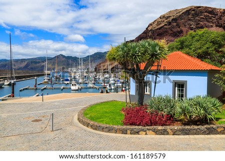 Coastal promenade in marina with moored boats and yachts and colorful house, Madeira island, Portugal  - stock photo