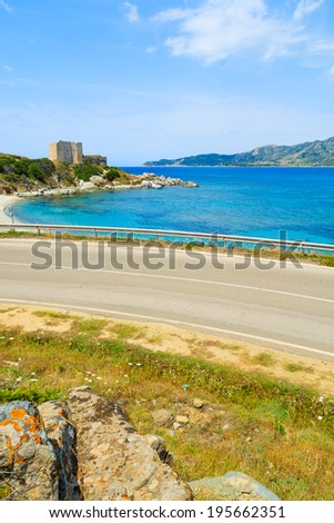 Coastal road along azure sea with castle in the background near Porto Giunco port, Sardinia island, Italy - stock photo