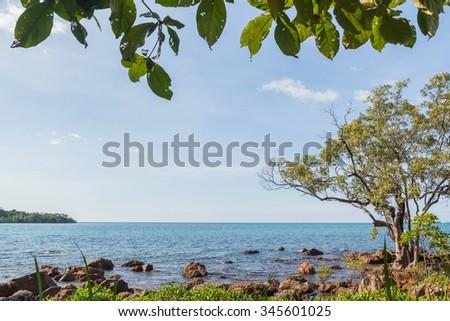 Coastal rock in deep blue sea - stock photo
