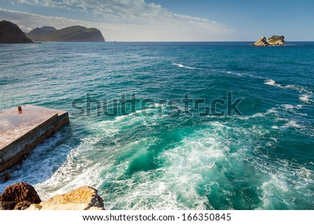 Coastal stones and small pier with breaking waves. Adriatic Sea - stock photo