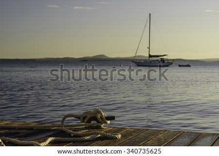 Coastal study in nautical preference: Rope tied to cleat on dock in foreground to secure a boat off camera, while a sailboat lies at anchor beyond, at sunrise in New England (foreground focus) - stock photo