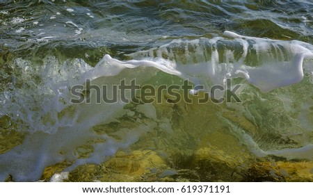 Coastal transparent sea/ocean crashing wave with foam on its top. Close up.