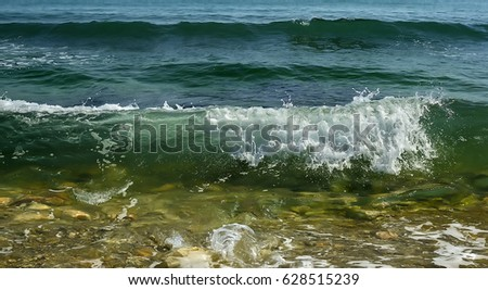 Coastal transparent sea/ocean crashing wave with foam on its top. Close-up.