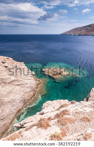 Coastal view from the hills on crystal clear turquoise water during a sunny day on Andros island, Greece - stock photo