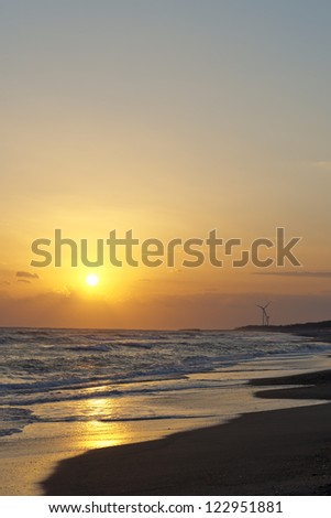 Coastal windmills during sunset in Japan - stock photo