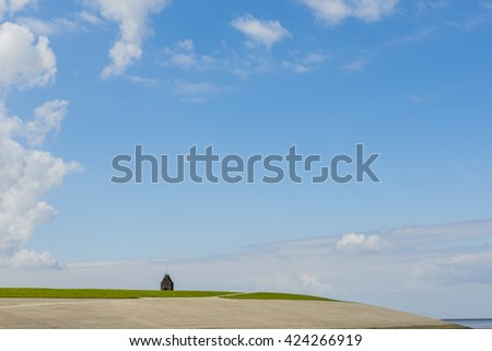 Coastline of the Waddensea at Friesland and dike. In the background the church of Wierum. - stock photo