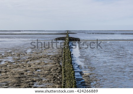 Coastline of the Waddensea at Friesland wit mud flats and protection poles and dikes. - stock photo