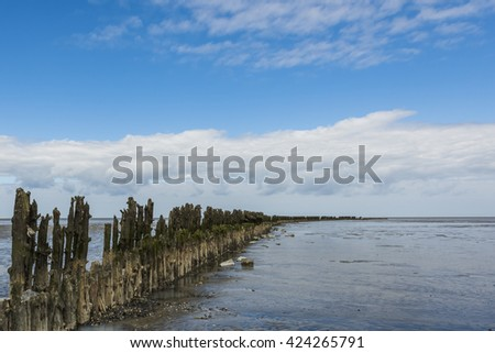 Coastline of the Waddensea at Friesland with mud flats and protection poles and dikes. - stock photo