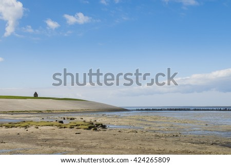 Coastline of the Waddensea at Friesland with mud flats, dike and protection poles and dikes. In the background the church of Wierum. - stock photo