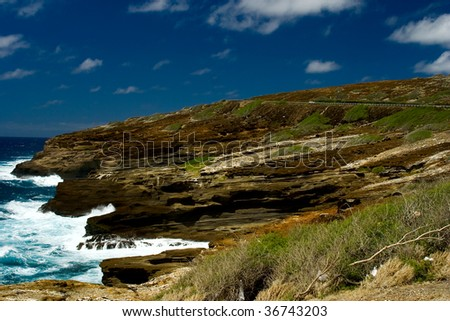 Coastline with with red rocks on the island of Oahu Hawaii