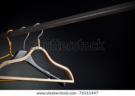 Coat hanger on a black background - stock photo