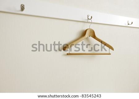 Coat hanger on white wall. - stock photo