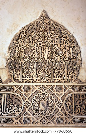 Coat of Arms of Nasrid Kings and arabic inscription on the wall of Alhambra, Palace of the Nazaries, in Granada, Spain. - stock photo