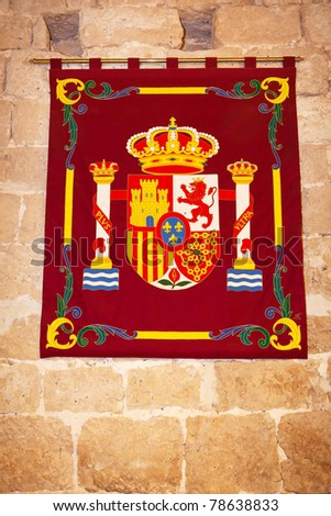 Coat of arms of The Spanish Crown in a tapestry hung on an ancient stone wall