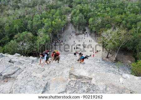 COBA,MEXICO - FEBRUARY 19: Group of tourists climb down the steep Nohoch Mul pyramid in Coba, Mexico on February 19, 2011. The main attraction to Coba is that you can climb the pyramid. - stock photo