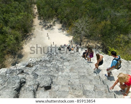 COBA, YUCATAN,MEXICO - MARCH 29: Group of tourists climb down the steep Nohoch pyramid in Coba, Mexico on March 29, 2010.The main pyramid in the ancient Mayan city of Coba in Mexico. - stock photo
