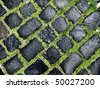 cobble road with grass growing between cobbles - stock photo