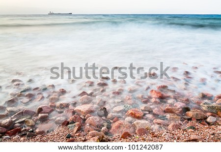 cobble stone beach of Red Sea on sunset, Jordan