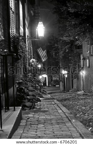 cobble stone road in Boston Massachusetts, lit  by the gas lamps revealing the shuttered windows and brightly lit doorways of the rowhouses on Acorn Street, you can almost feel the night coming down - stock photo