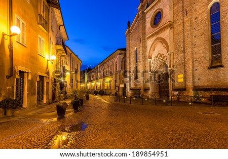 Cobbled street between old church and houses with lampposts early in the morning in Alba, Italy. - stock photo