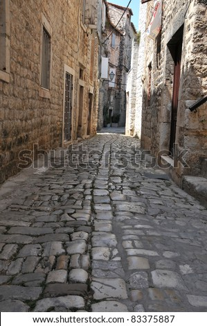 Cobbled street winding through quiet old town, inviting for tourists on holiday