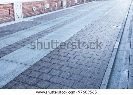 cobblestone paved road long to the light - stock photo