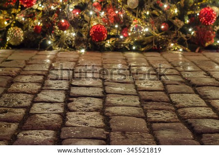 Cobblestone pavement and christmas decorations on background - stock photo