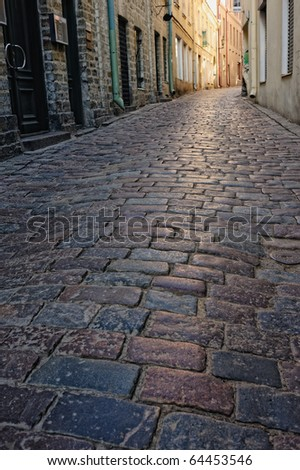 Cobblestone pavement in the narrow street in old town - stock photo