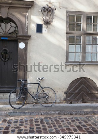cobblestone street with bicycle and medieval houses Riga Latvia Europe   - stock photo