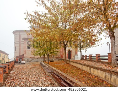 Cobblestone walkway, trees and small parish church on background in foggy autumnal morning in Piedmont, Northern Italy.