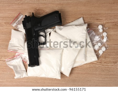 Cocaine and marihuana in packages and handgun on wooden background - stock photo