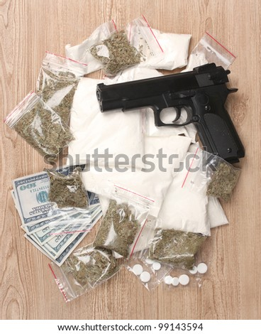 Cocaine and marihuana in packages, dollars and handgun on wooden background